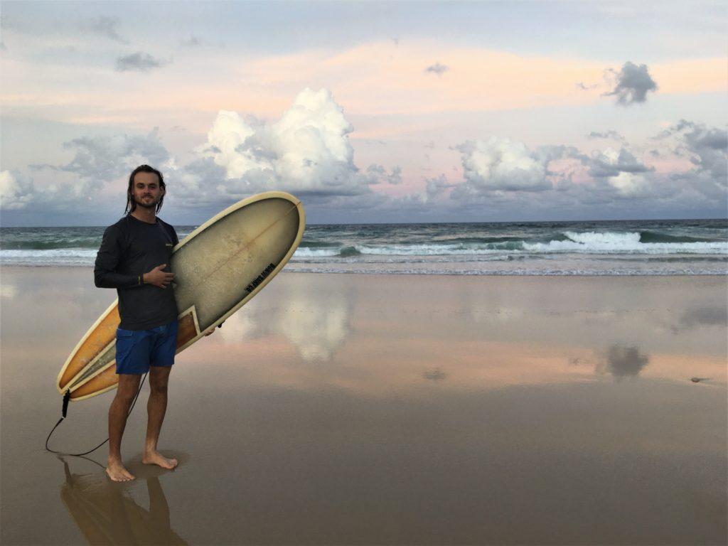 Adam se surfem při západu Slunce, Broadbeach, Gold Coast, 2020