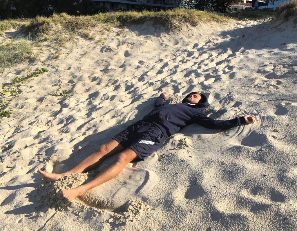 Adam v písku na pláži Broadbeach, Gold Coast, 2020